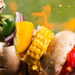 Tongs placing skewered vegetables on a flaming grill