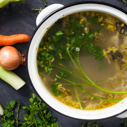 Vegetables next to a bowl of soup broth
