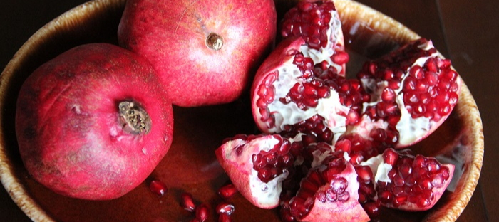 Two whole pomegranates and one open pomegranate