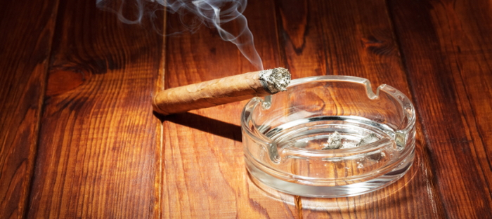 Smoking cigarette against a glass ashtray