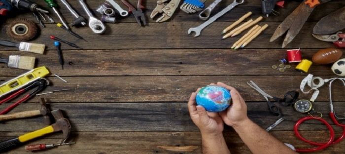 hand tools and a person holding a miniature earth