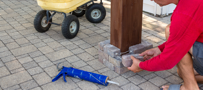 Man placing stone bricks at base of post