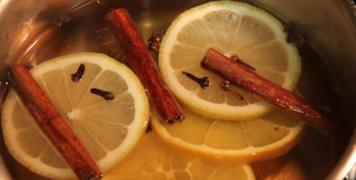 Citrus slices and spices in a saucepan