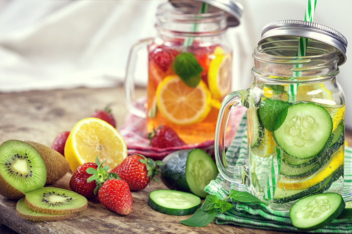 Two glass jars of fruit infused liquids with fruit slices