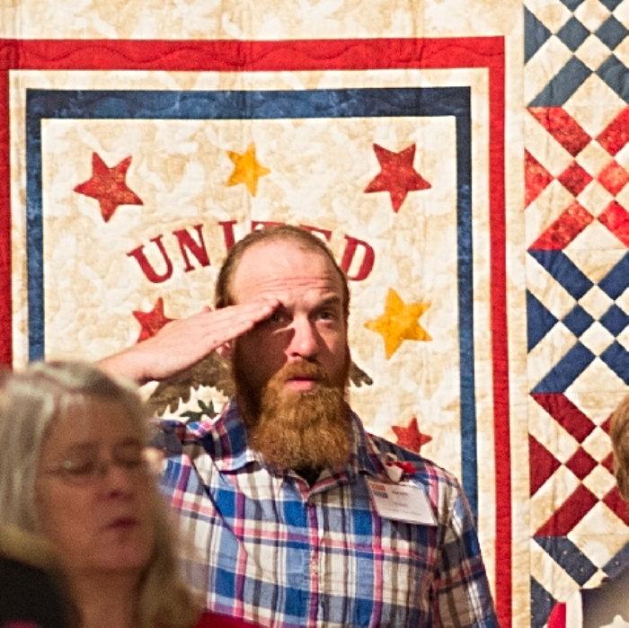 man saluting a quilt