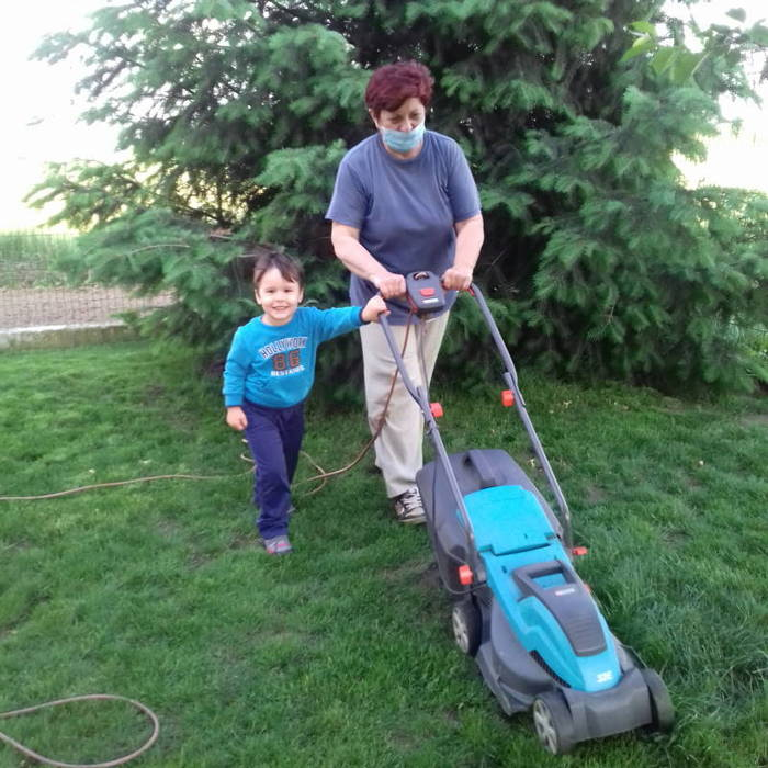 Me wearing a mask while mowing the lawn with my grandson