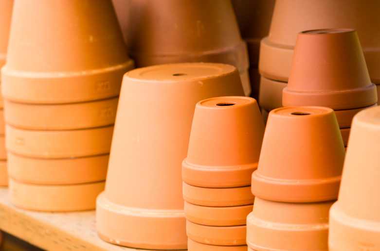 Stacks of clay planting pots with drainage holes