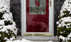 Christmas wreath on the front door of a house, surrounded by snow-covered bushes.