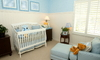 A white baby crib in a blue-themed nursery.