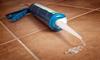 A tube of silicone caulk dispensing on a tile floor.