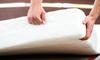 A man lifts a foam mattress.