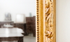 A decorative gold mirror hanging on the wall.