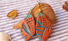 clay earrings on a striped fabric background with shells and leaves