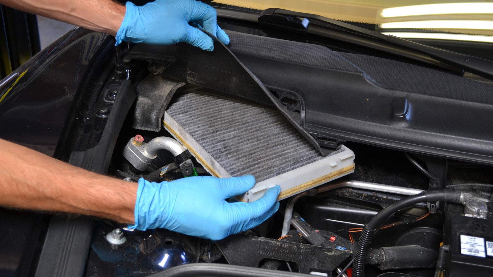 Человек носит перчатки, чтобы работать внутри автомобиля.