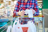 A woman in a plaid shirt looking at a receipt over a shopping cart with a plastic bag in it.
