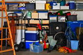 Storage containers on shelves in a garage, with odds and ends scattered about.