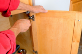 Man using a screwdriver to turn the screw on a cabinet hinge