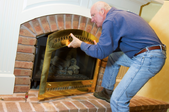 man removing front of a fireplace