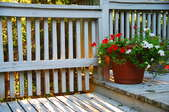 porch with white wooden railings and flowers