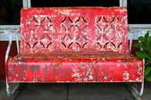 A red, rusty antique bench.