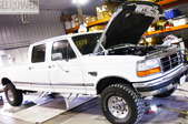 White Ford truck with hood up in a shop