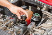 A hand removing the cap to the oil reservoir under the hood of a car.