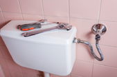 Tools laying on the top of a toilet tank