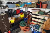 A cluttered mess takes over the space inside a garage.