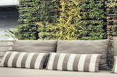 A vertical garden behind some patio furniture.