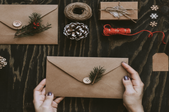 A pair of hands holding a kraft paper envelope surrounded by diy supplies for making holiday cards.