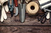 Various garden tools laid out on a wooden table.