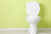 white toilet sitting against a yellow wall