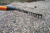 Using a rake to level a gravel driveway.