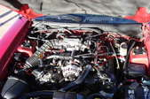 The engine under the hood of a red car.