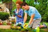 A young, cheerful couple planting flowers