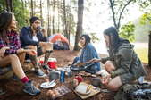 A group of friends gathering around a meal while camping.