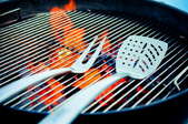 A grilling fork and spatula on a burning barbecue.