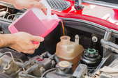 Someone pouring transmission fluid in a car.