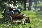 A man on a riding lawn mower.
