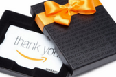 An amazon gift card in a black box with an orange bow