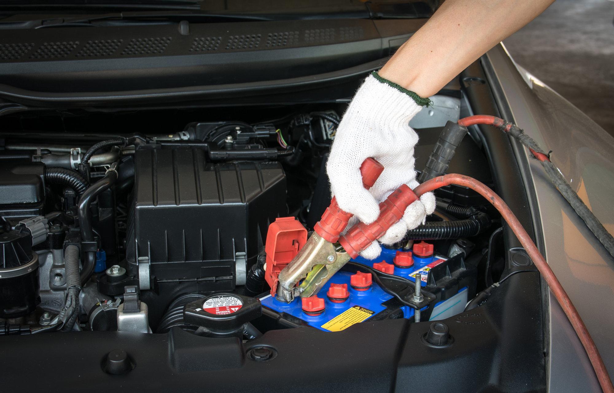 Автомобильный аккумулятор внутри капота автомобиля.