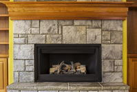 A stone fireplace with an insert.