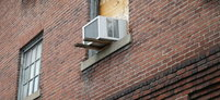 A window in a brick apartment with an air conditioner in it.