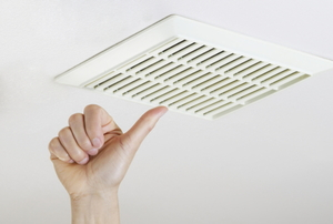 Hand touching a white bathroom ceiling vent.