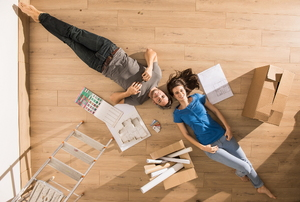 A couple laying on the floor dreaming about their home improvement plants with a box and ladder next to them.
