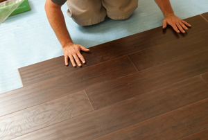 Snap-together laminate wood flooring covering a concrete subfloor.