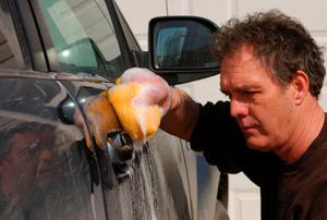 A disgruntled man applies elbow grease to his car.