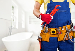 plumber wearing a tool belt and holding a large wrench