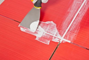 A putty knife scraping grout on red tile.