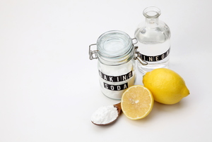 A jar of baking soda and vinegar against a white background with a couple of lemons.